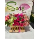 Baúl de madera con chocolates y rosas rojas